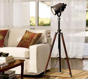 Sala de estar composta por paleta de cores claras e destaque para a luminária de três de pés e cúpula em estilo industrial