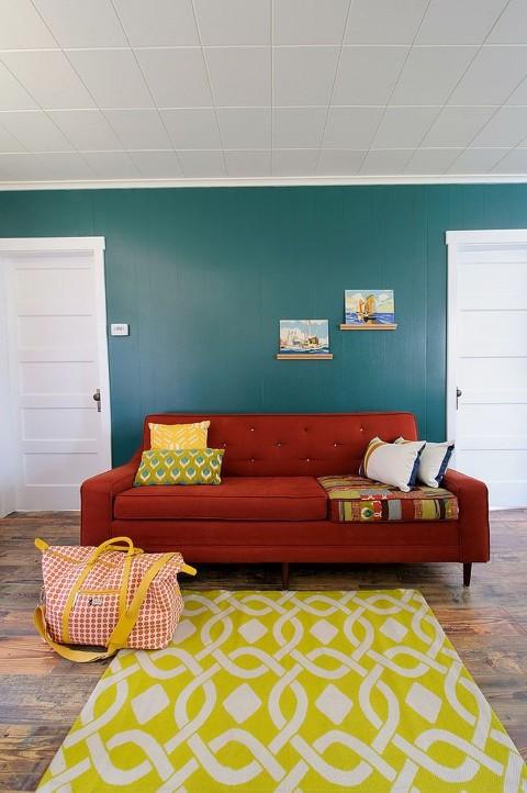 O sofá vermelho na sala de estar vai destacar os demais elementos do seu ambiente