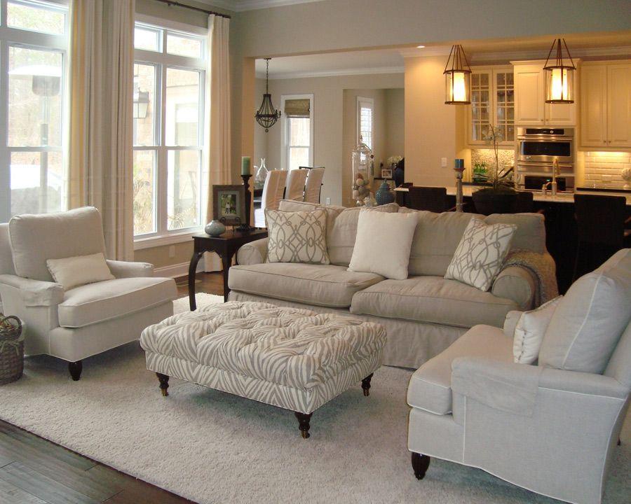 A mesa de centro estofada segue o mesmo padrão de pés palito que as poltronas, causando equilíbrio na decoração