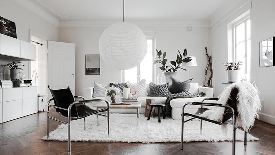 Poltronas gêmeas com estofado preto em conjunto com tapete, sofá e pendente na cor branco