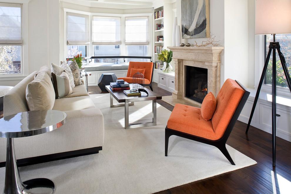 Em contraponto a tonalidade clara da sala de estar, as poltronas sem braços na cor laranja são destaque